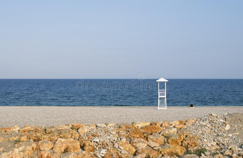Seascape with lifeguard hut on calm sky background. Beach with lonely man. Minimal summer seascape with lifeguard hut on calm sky background. Beach with lonely stock image
