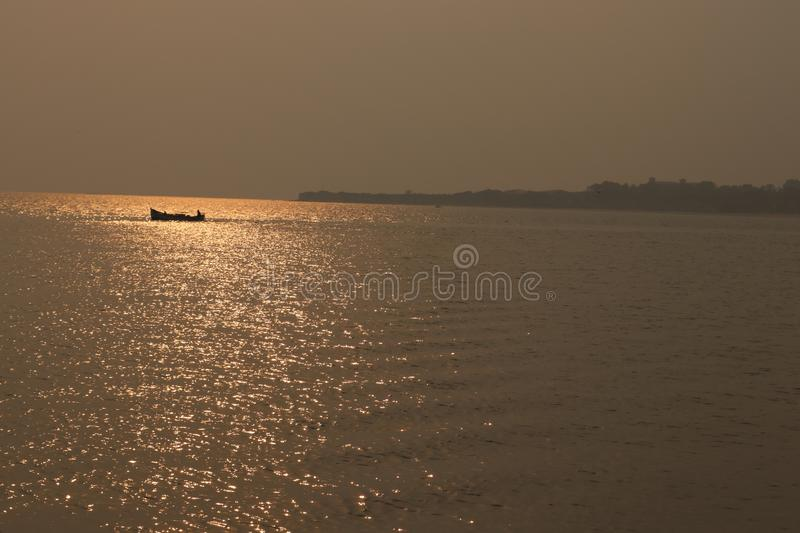 Seascape, lonely boat with sailor in a calm sea at beautiful sunset with sun reflection in the water royalty free stock photography