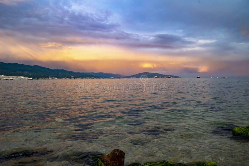 Seascape med berg och härlig himmel på solnedgången arkivbilder