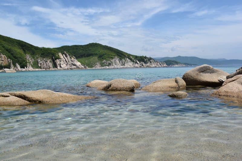 Seascape med berg och klart vatten royaltyfri fotografi
