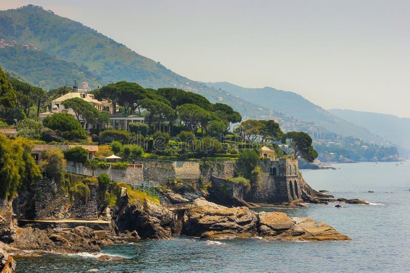 Seascape med den medelhavs- steniga kustlinjen och promenaden på Genoa Nervi royaltyfria foton