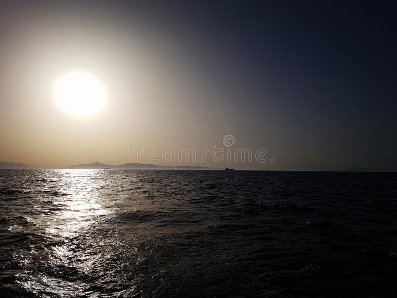 Seascape med en ö vid horisonten i gryningen arkivfoton