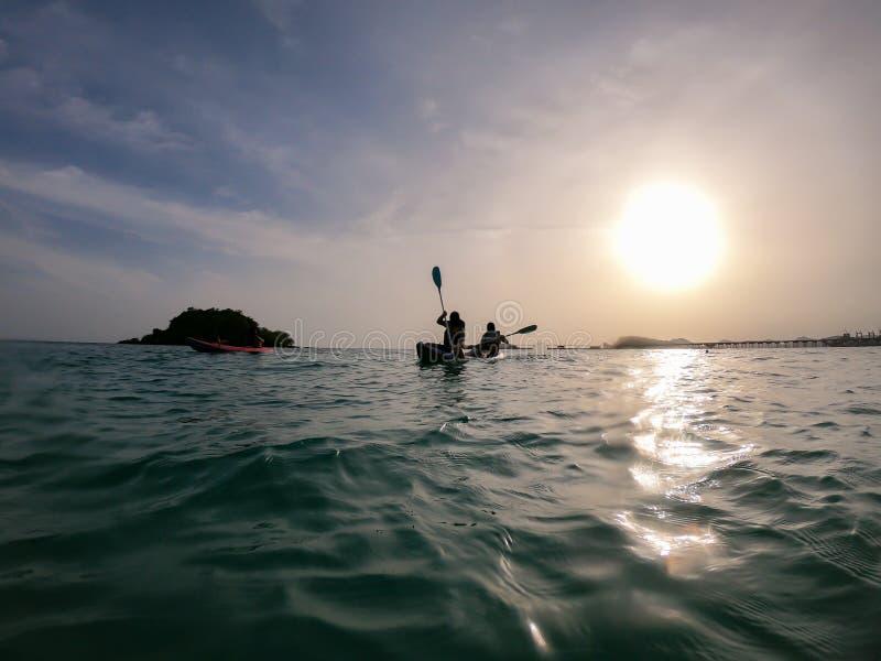Seascape med kayakers på solnedgången konturman i kajaken på havet framme av den dramatiska solnedgången royaltyfria foton