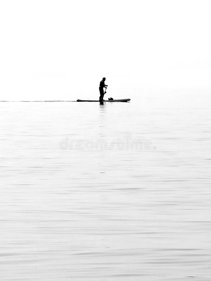 Seascape and natural landscape view lonely paddler with christal water on the beach of Lazise Lake Garda, Italy royalty free stock photo