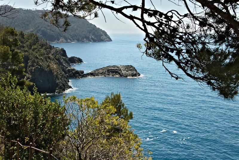Seascape near the Cinque Terre, in Liguria, Framura, Italy. A blue sea with sheer mountains. Mediterranean trees stock image