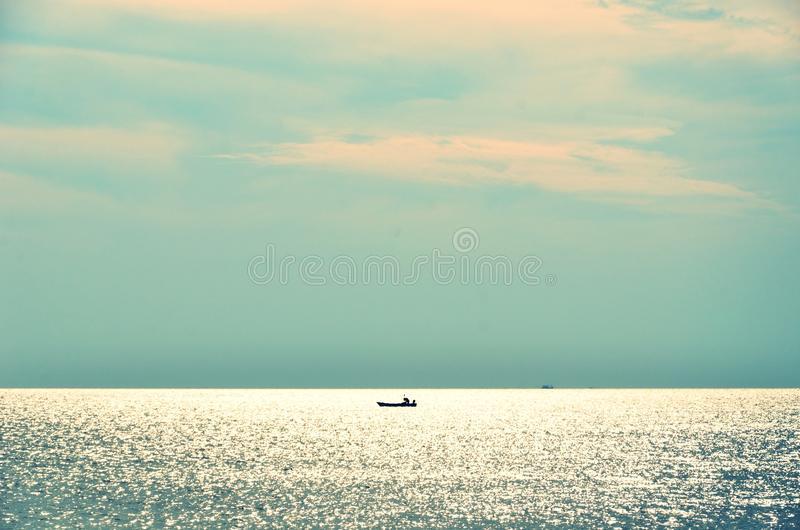 Seascape with nice sky color and lonely ship at the horizon royalty free stock image