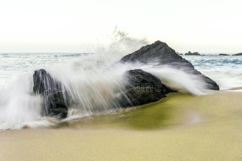 Seascape with the ocean in motion at sunset in sandy Adraga Beach stock photography