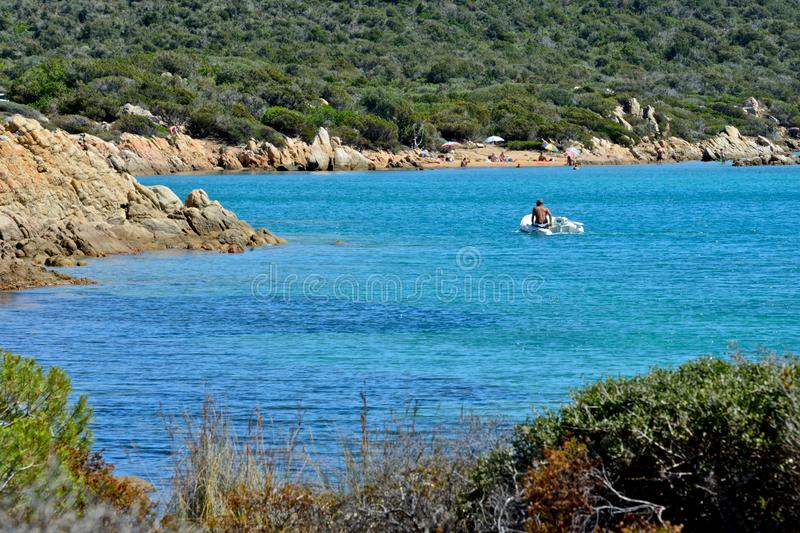 Seascape with one man on a little motor boat in a blue sea surrounded by wild nature royalty free stock image