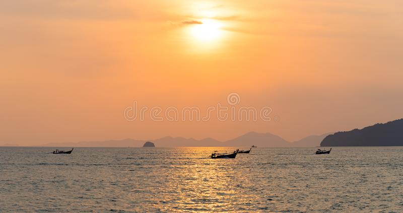 Panorama of local thai longtail motor boats under golden sun in the sea water at orange sunset in Ao Nang in Krabi royalty free stock image