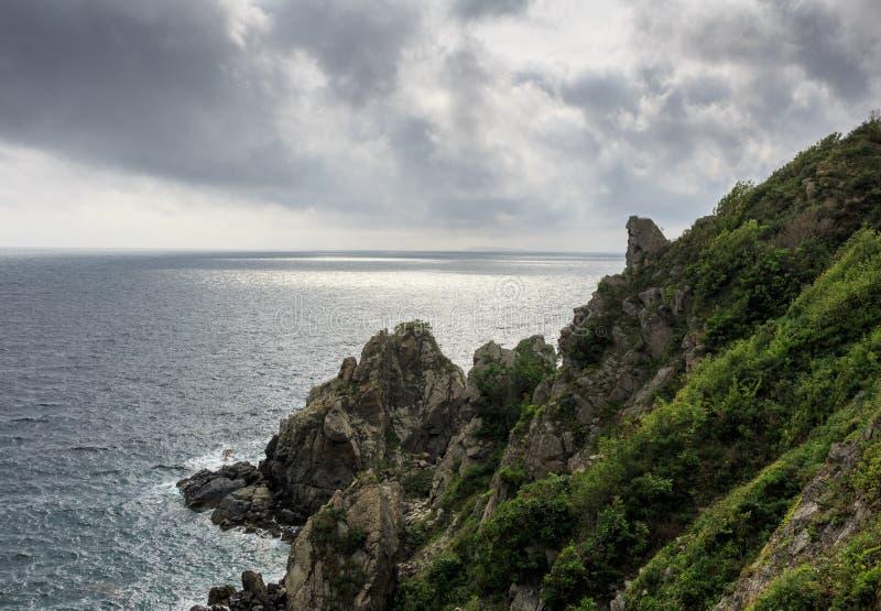 Seascape przegapia ciemnego chmurnego niebo stalowego morze i skały wysokie, niebezpieczne, zdjęcie royalty free