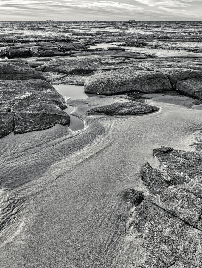 Seascape rocky beach with large rocks and boulders in calm sea water black and white image royalty free stock photos