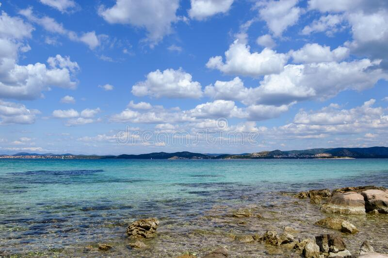 Seascape with rocky beach and white clouds stock photos