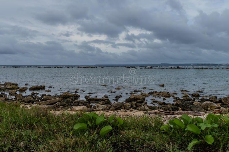 Seascape of rocky shoreline on a cloudy day. With buildings on tree lined shore in the distance stock photo