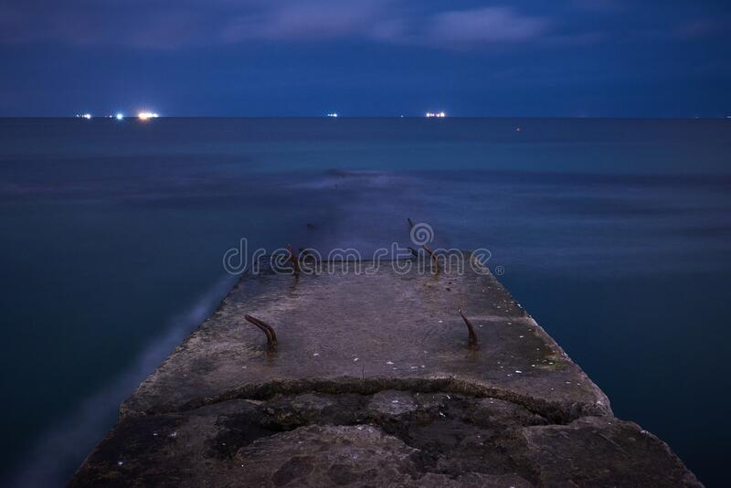 Seascape with sea wave cutter and soft water. shot taken at night with long exposure stock photo