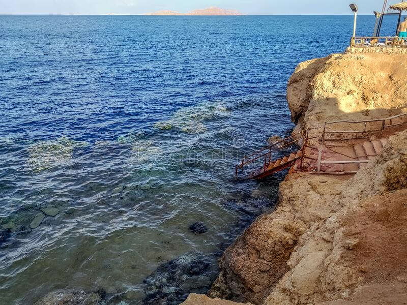 Seascape in Sharm El Sheikh Egypt and Tiran Island on the horizon. An old rusty metal staircase descends from a cliff to a coral. Reef in the Red Sea royalty free stock photography
