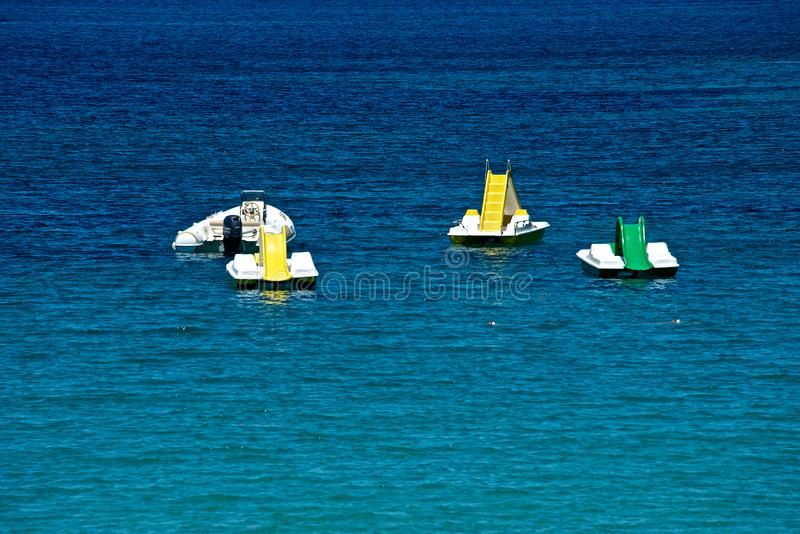 Seascape with some pedalos and boats royalty free stock photos