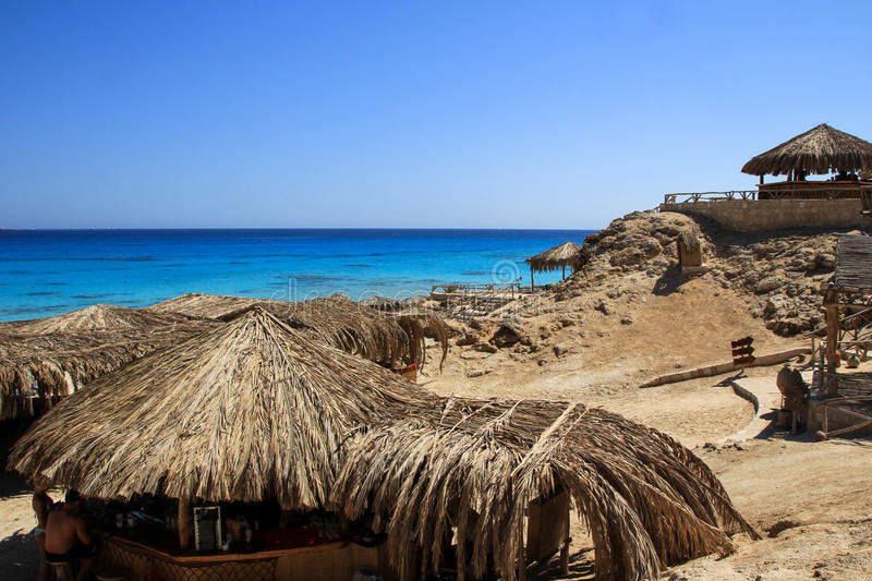 Seascape with straw umbrellas and horizon line. Tourism in Egypt, May 2012 stock photography