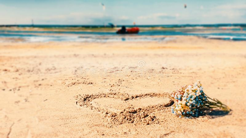 Seascape Summer beach on sand bouquet wild flowers and heart  sign blue sea water on horizon romantic background stock photos