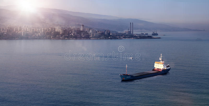Seascape Sunrise in Jounieh, Lebanon. A cargo ship floating on water facing a bay during sunrise, in Lebanon stock photos