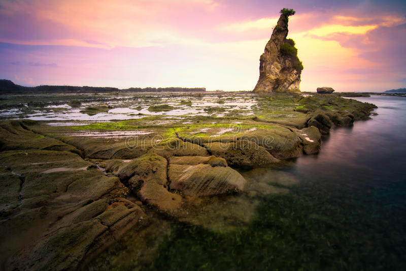 Seascape sunset scenery at Sawarna beach, Banten, Indonesia. Beautiful seascape scenery of big boulder stone during sunset at Tanjung Layar beach in Sawarna stock image