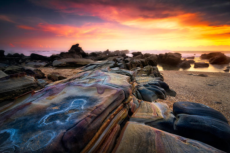 Seascape sunset scenery at Sawarna beach, Banten, Indonesia. Beautiful seascape sunset scenery with colourful stone as foreground during sunset at Tanjung Layar royalty free stock photography