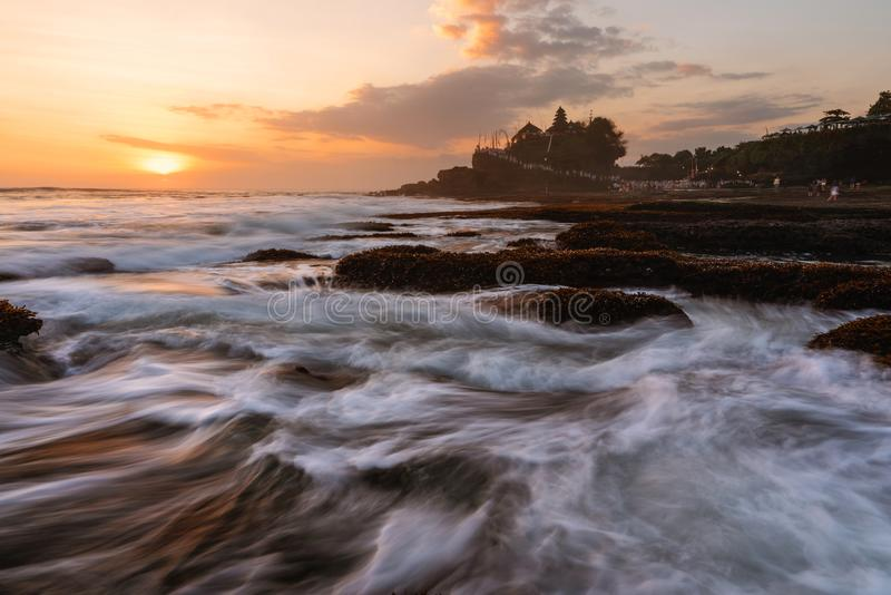 Seascape in sunset with strong wave at Tanah Lot Temple in Bali, Indonesia. Famous landmark tourist attraction and travel destinat. Ions royalty free stock photo