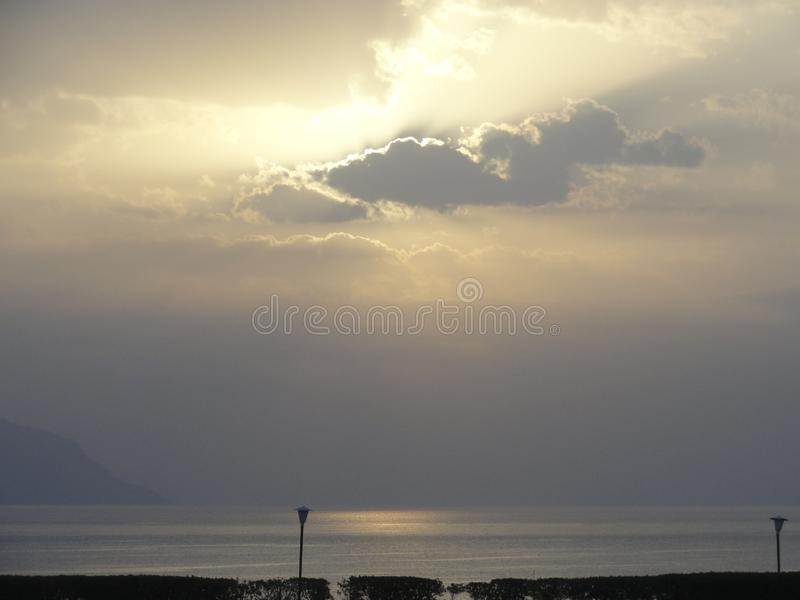 Seascape - sunset, the sun sets in the formidable storm clouds over the sea. royalty free stock image