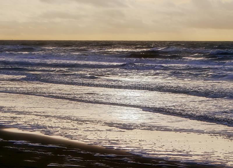 Seascape, the surf area of ​​a beach in the back light just before dusk begins. France. Atlantic coast breton stock photography