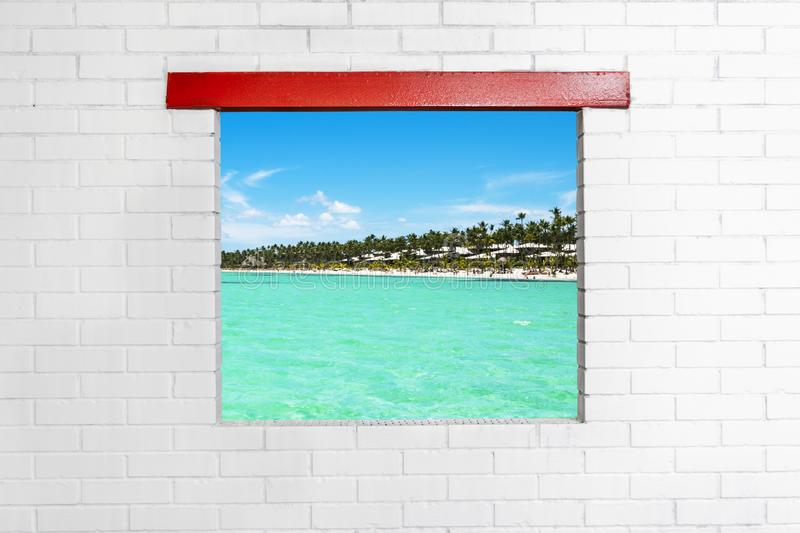 Seascape tropical view from window on brick wall. Beautiful tropical beach and blue sky. Ocean with turquoise water and tropical i. Sland. White brick wall and a stock photography