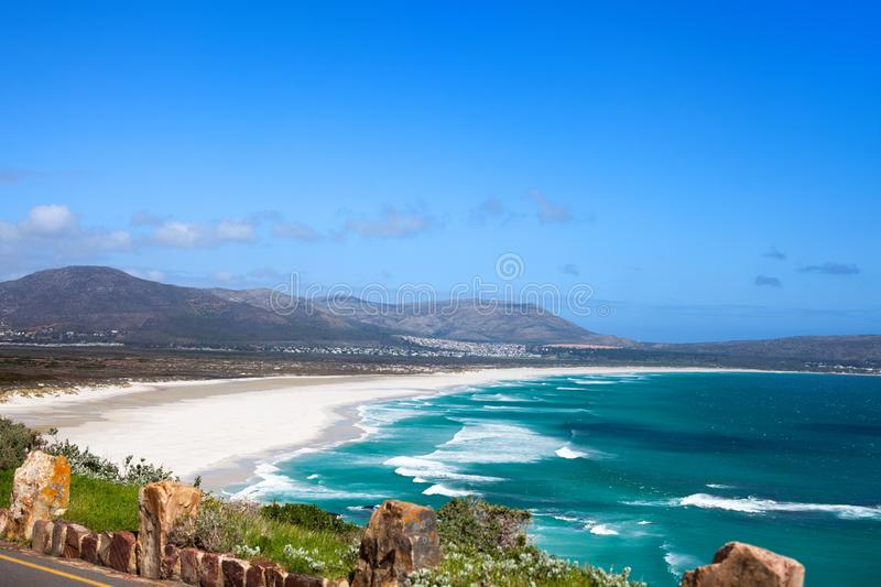 Seascape, turquoise ocean water waves, blue sky, white sand lonely beach panorama Chapmans Peak Drive road, South Africa coast t royalty free stock photos