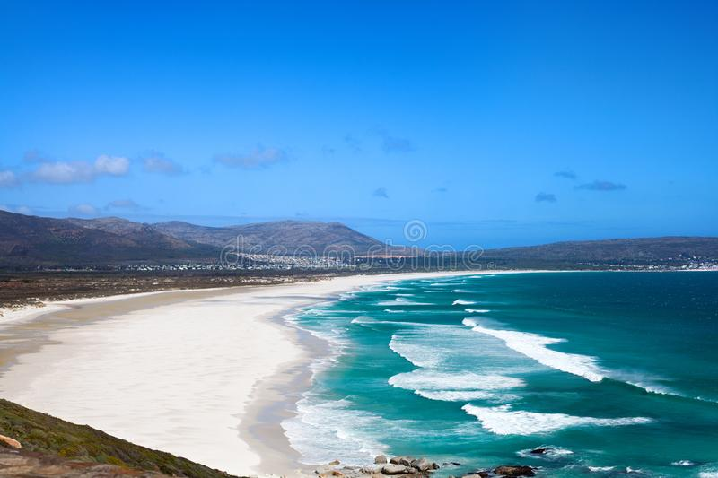 Seascape, turquoise ocean water waves, blue sky, white sand lonely beach panorama Chapmans Peak Drive road, South Africa coast t stock photography