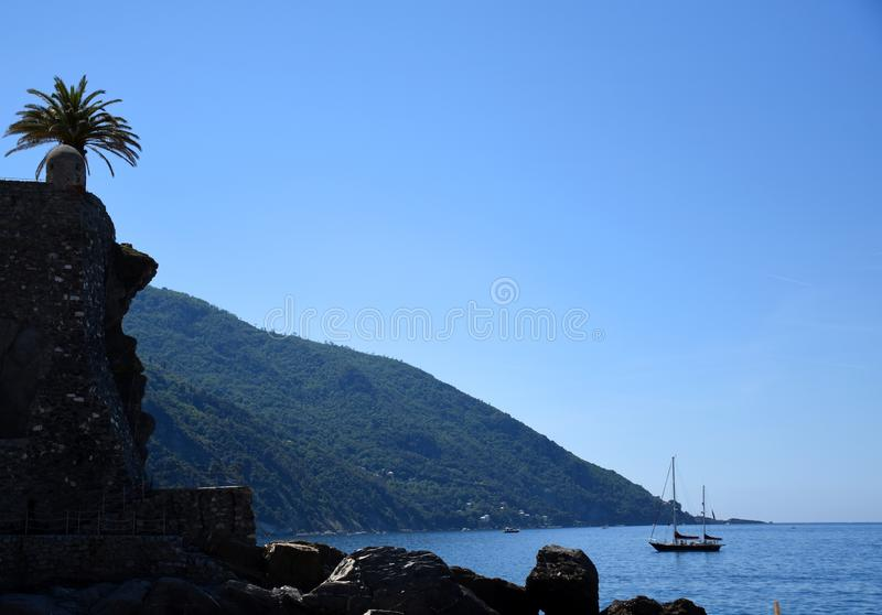 Seascape view with rocky beach and a sailing boat stock photography