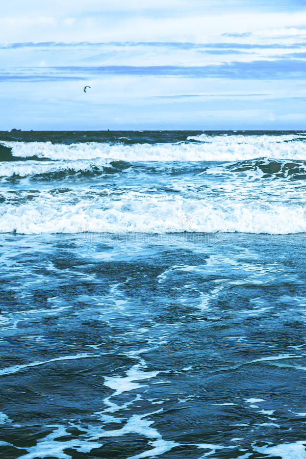 Seascape with waves, ship and kitesurfer. S on horizon royalty free stock image