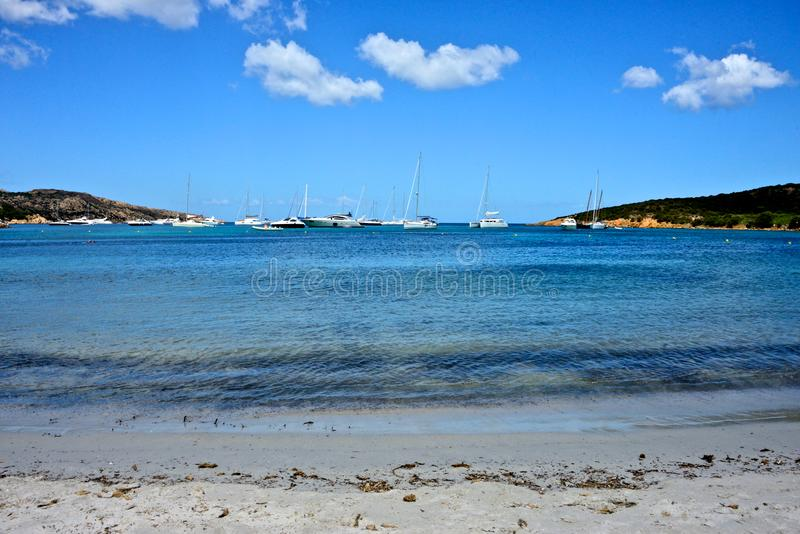 Seascape of white sandy beach with some yachts royalty free stock photography