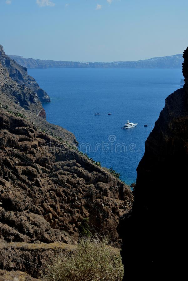 seascape through a wild landscape and a yacht anchored in front of Santorini royalty free stock image
