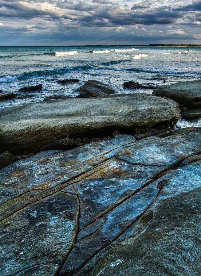 Seascape z błękitnawymi skałami i głazami w wod morskich wave's miękkim niebie z chmura surfingowami w odległości fotografia royalty free