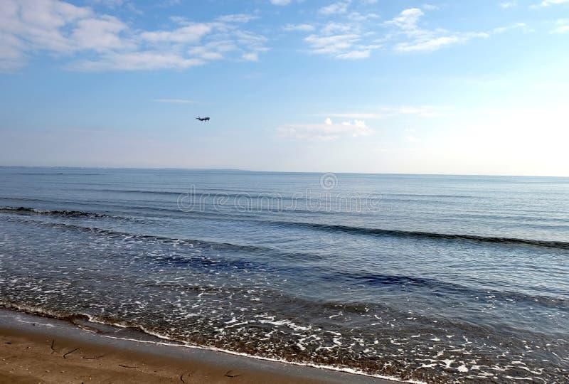 Seascape z pasażerskim samolotem gotowym lądować nad spokojny morze piaskowata plaża na słonecznym dniu i fotografia stock