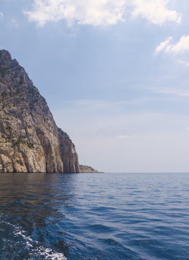 Seascape z skałą na horyzoncie, macha i chmurnieje obrazy royalty free