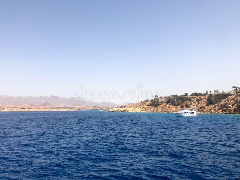 Seascapen av de avlägsna härliga tropiska bruna stenbergen och de olika byggnaderna, skeppet på kusten och den blåa salen royaltyfri foto