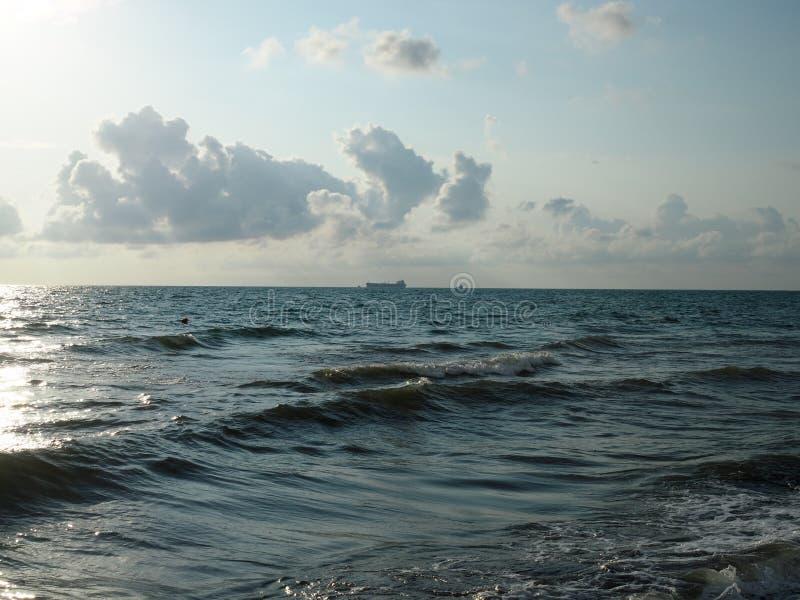 seascapes Различные виды красочных голубого неба, солнца, облаков и открытых пространств Мирового океана Силуэт сиротливой шлюпки стоковые изображения rf