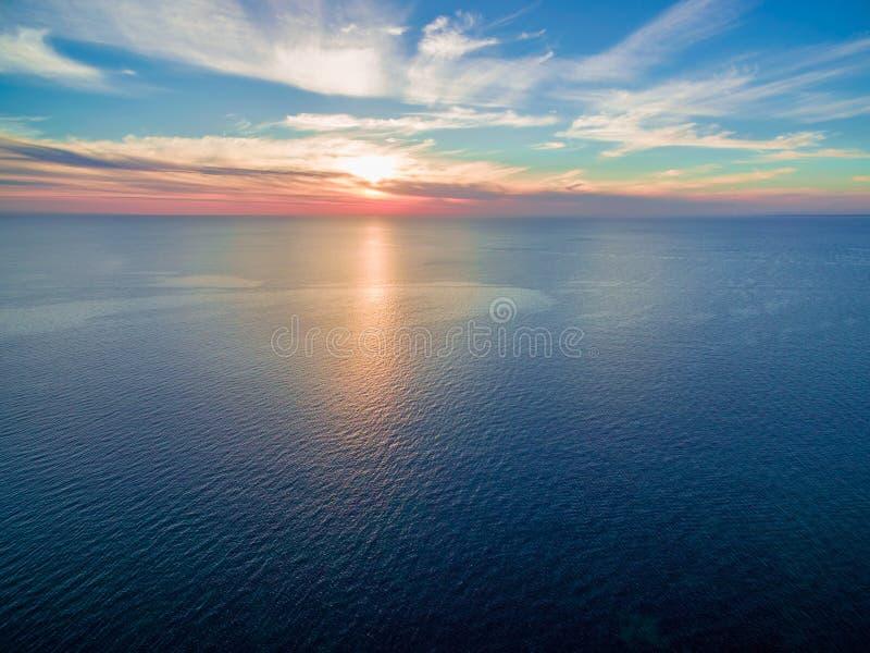 Seascapesolnedgång - sol som ställer in över det stillsamma havet royaltyfri bild