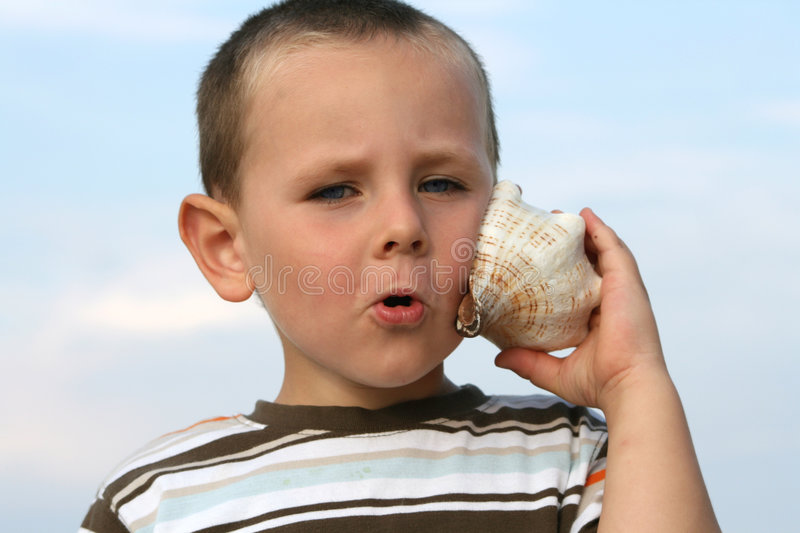 Seashell. 3 years old boy listening the sound of the sea in a seashell stock photography