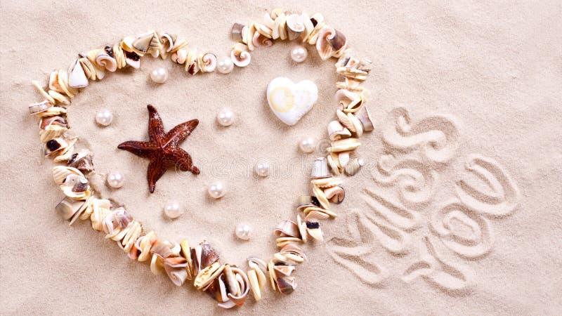 Seashell heart in sand stock photo