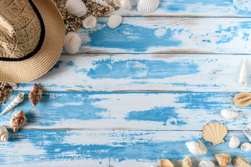 Seashells na błękitnej drewnianej desce z słomianym kapeluszem obraz royalty free