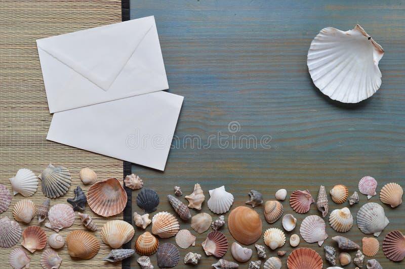 Seashells na cyan drewnie z puste miejsce listem zdjęcie stock