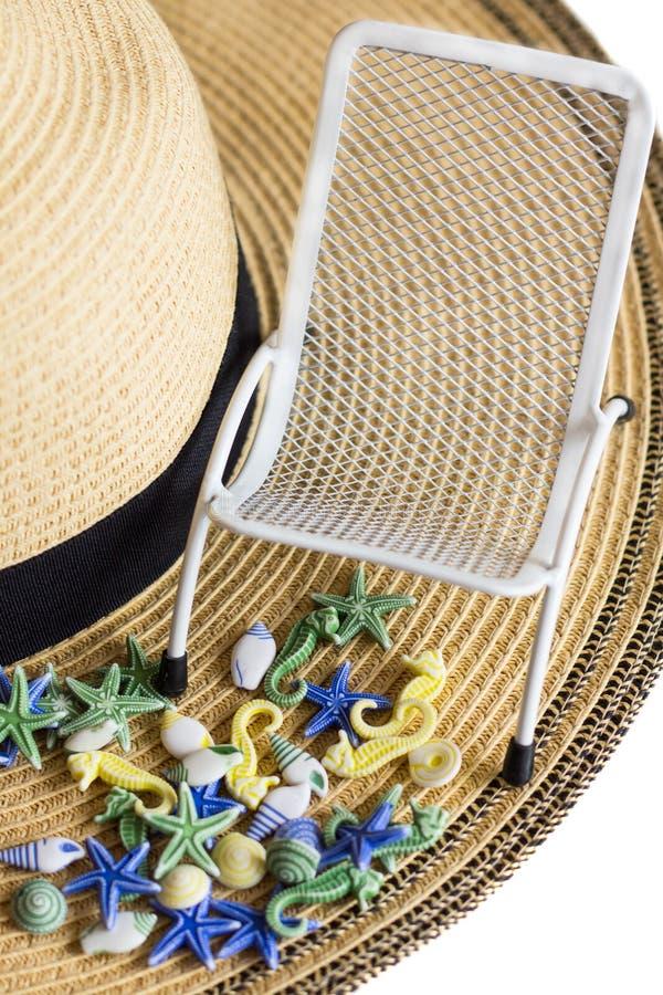 Seashells, sunbeds na tle lato słomiany kapelusz zamykający up, odizolowywający, pionowo fotografia royalty free