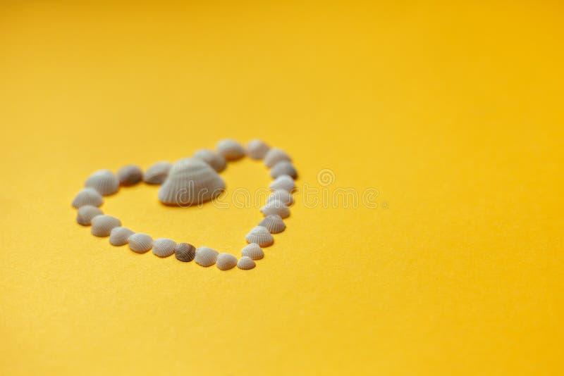 Seashells w formie serca na żółtym tle zdjęcie royalty free
