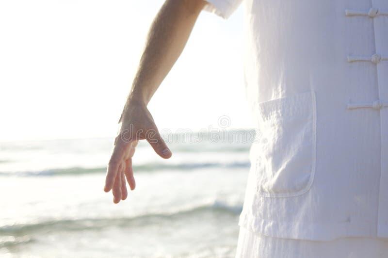 Персона в белой рубашке стоя на Seashore во время дневного времени стоковая фотография rf