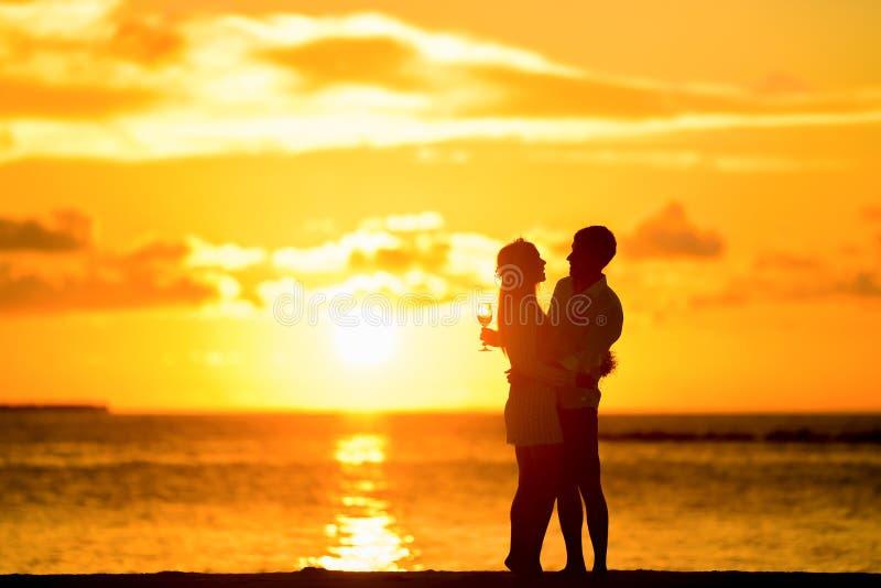 Пары стоя в Seashore обнимая один другого во время захода солнца стоковая фотография