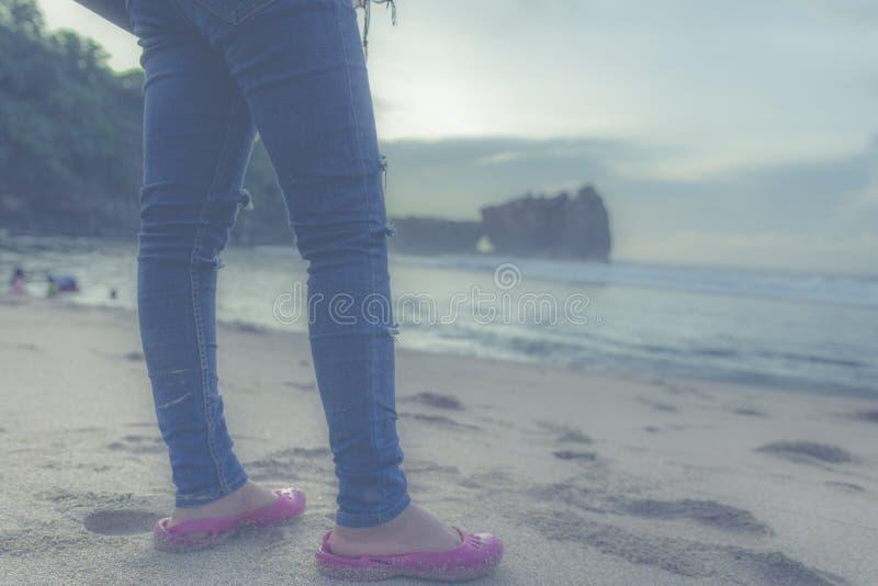 Персона в голубых джинсах и розовых квартирах перед Seashore стоковые фотографии rf